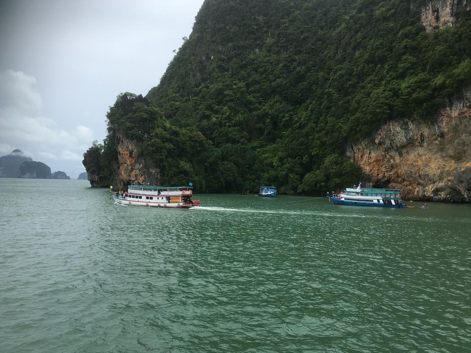 Cave,Tourists kayaking through limestone cliffs in Phang-nga Bay