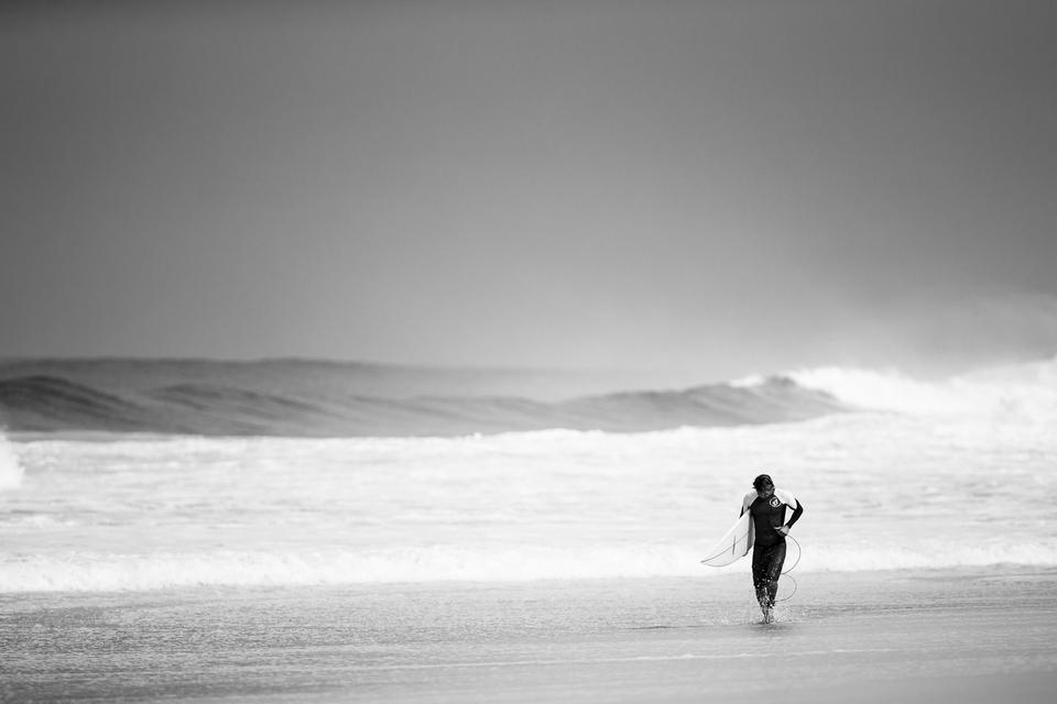 A man is walking with a surf in his hands across the sea shore