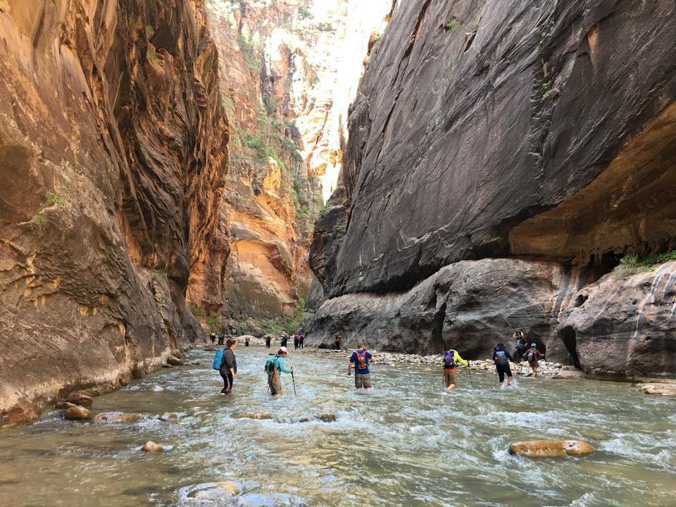 冷たい川でハイキングする観光客のグループ