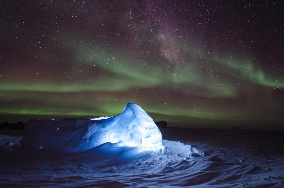 Aurora australis dancing over an LED illuminated igloo