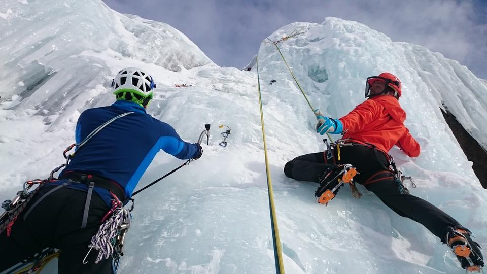 A young climber climbs on ice climbing