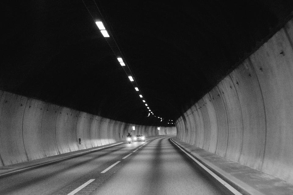 Black and white image of a man riding a scooter into a tunnel