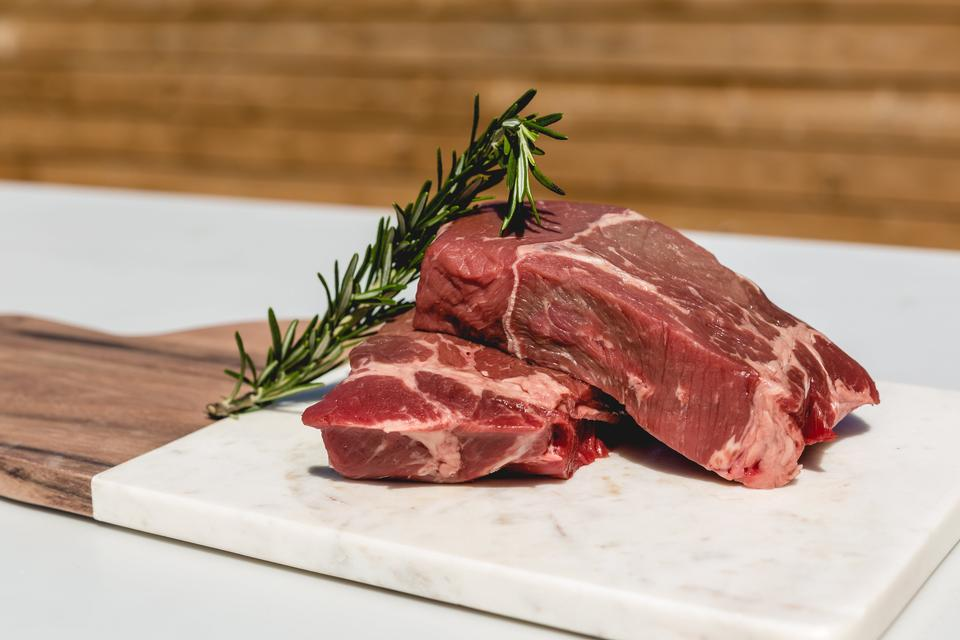 Two well-marbled steaks and some rosemary