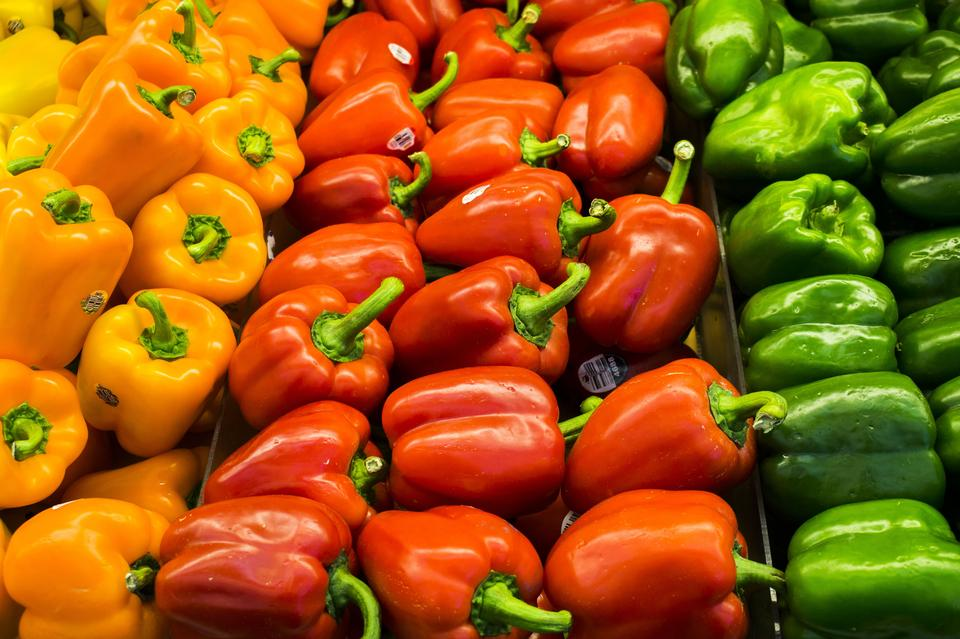 Red, orange and green peppers at a vegetable market all piled up