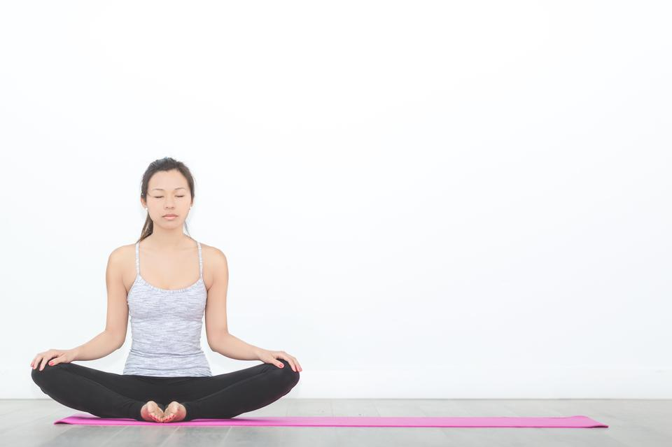 Woman in seated meditation pose on pink yoga mat