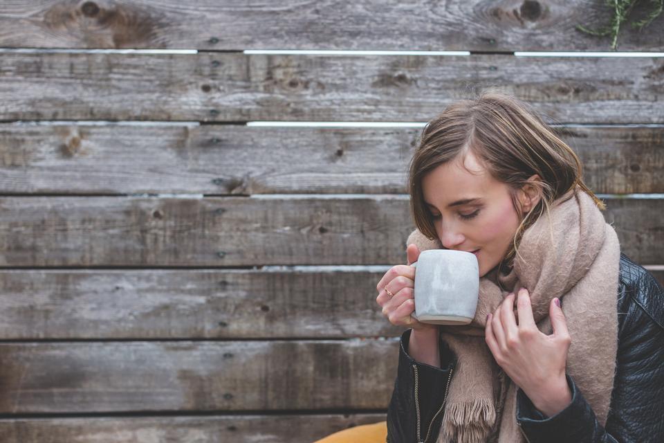 Femme blonde dans une écharpe de couverture et une veste en sirotant un café