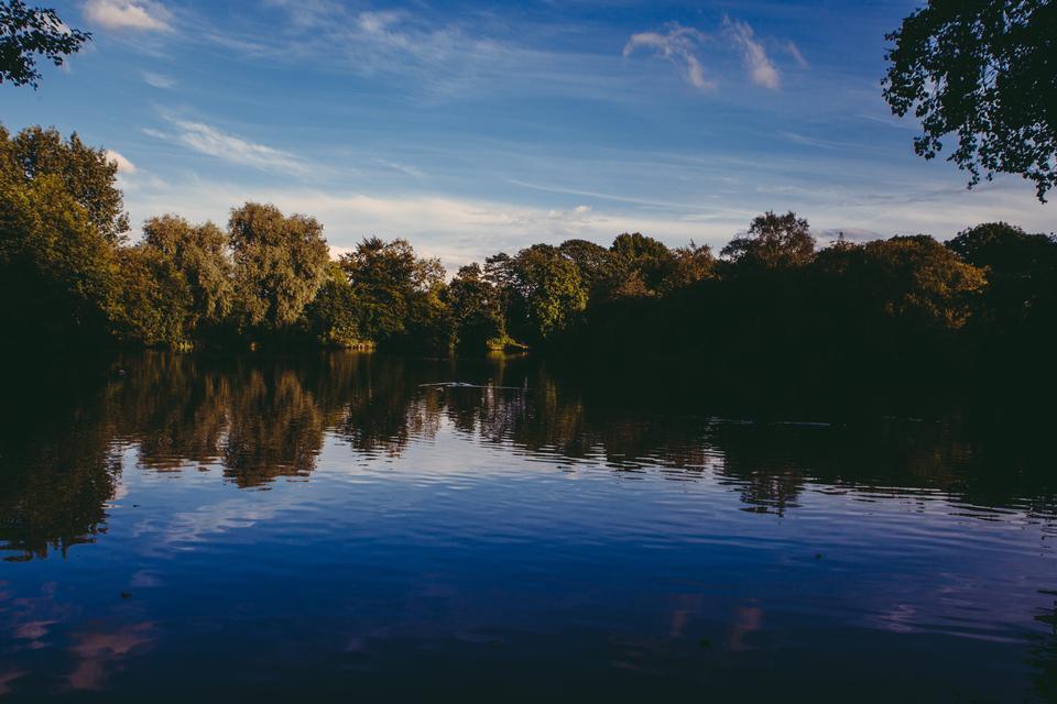 與藍藍的天空和陽光山反映在湖上