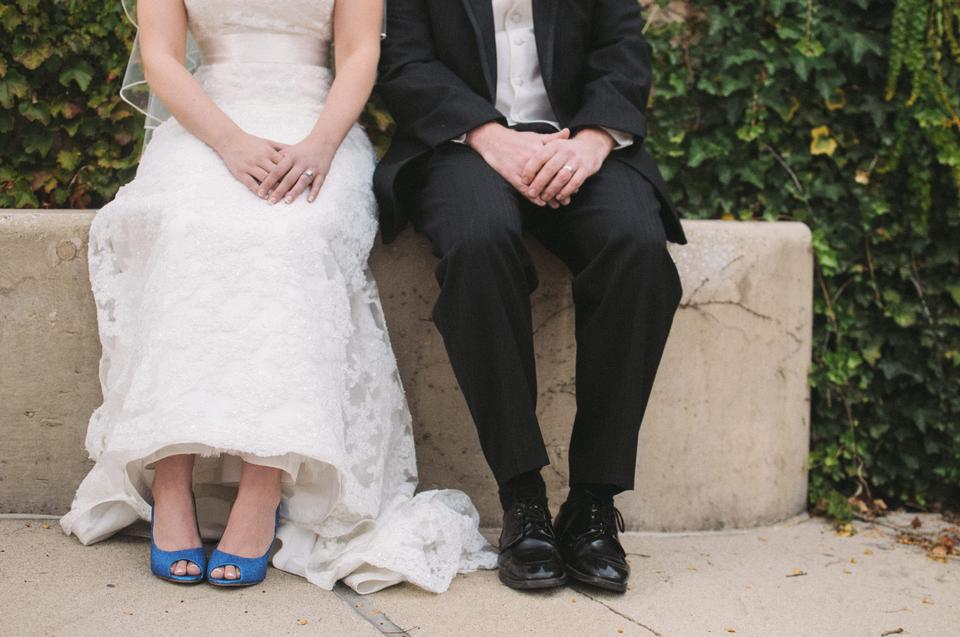 the bride and groom sit on a bench