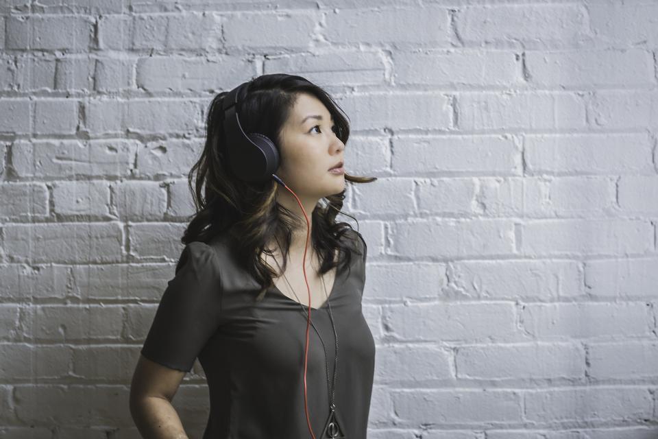 woman wearing black headphones listening to music