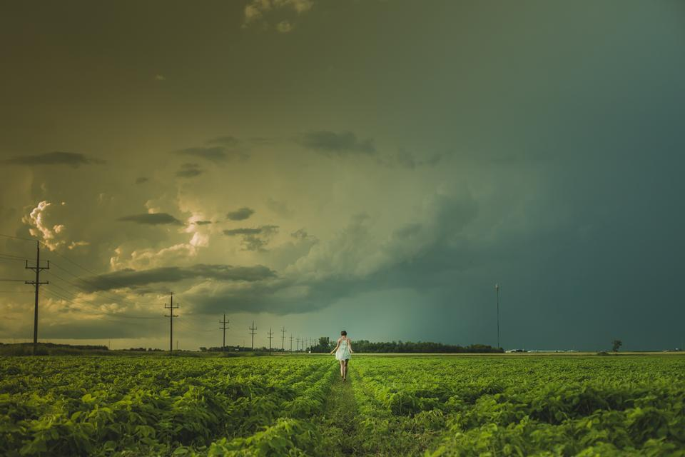 woman in a white dress walks through Manitoba prairie fields