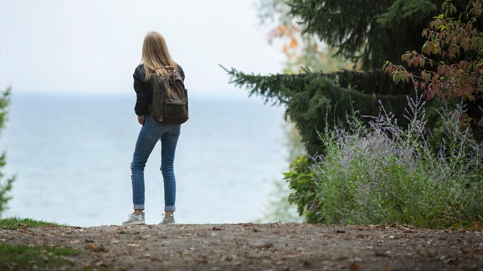 年輕女子徒步旅行者在美麗的山中徒步旅行
