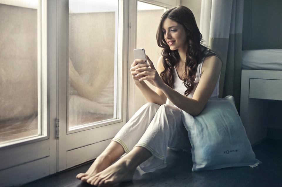 Belle jeune femme à l'aide de téléphone intelligent