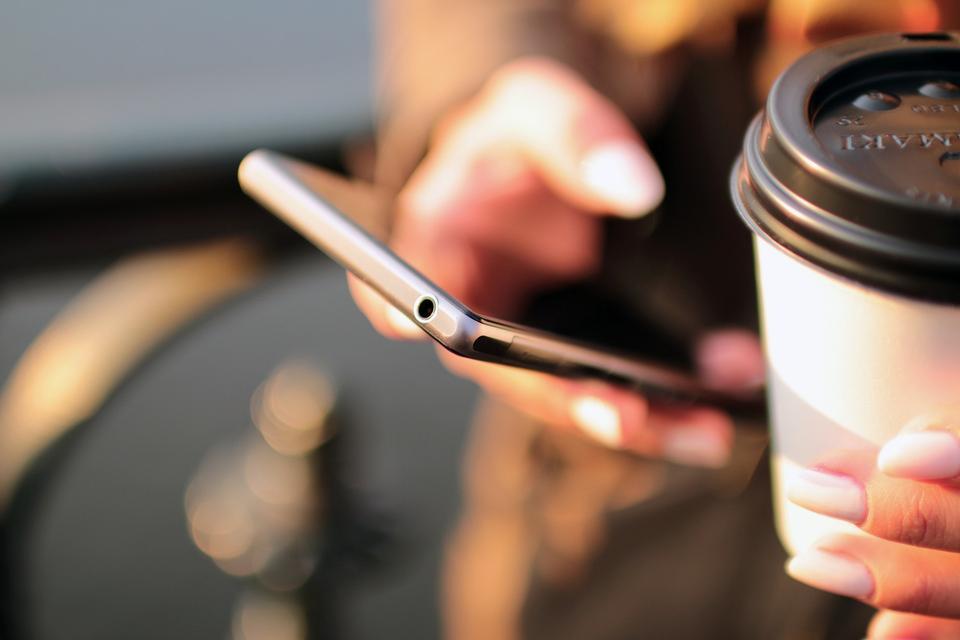 Gros plan des mains de femmes tenant un téléphone cellulaire