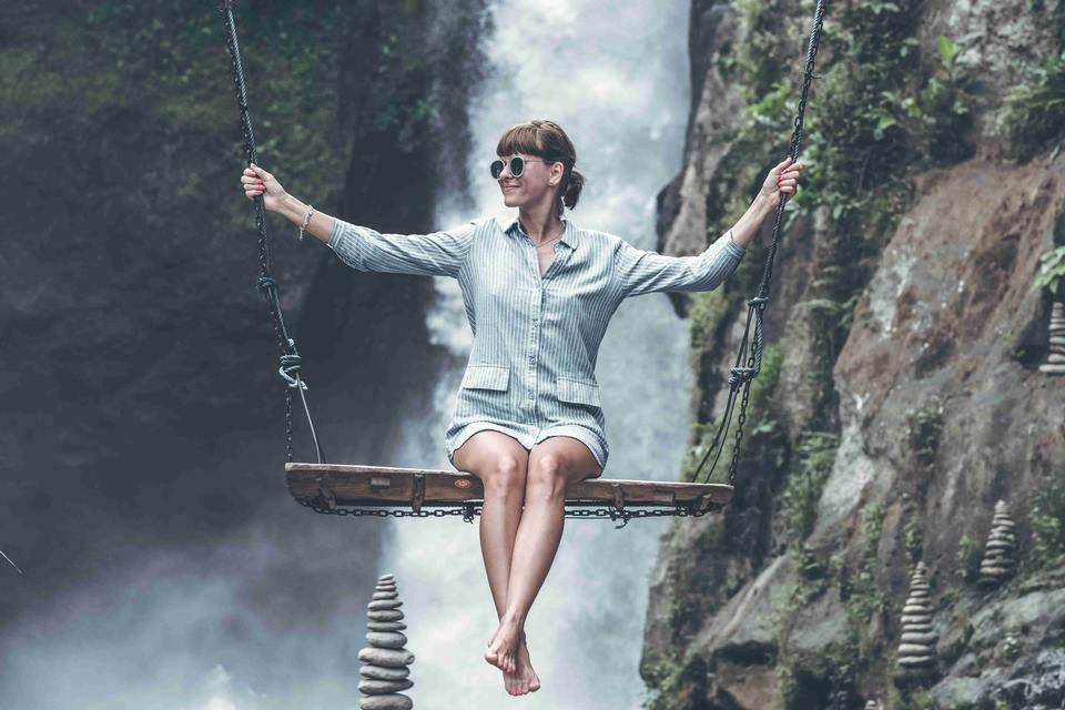 Woman swinging in the jungle of Bali island