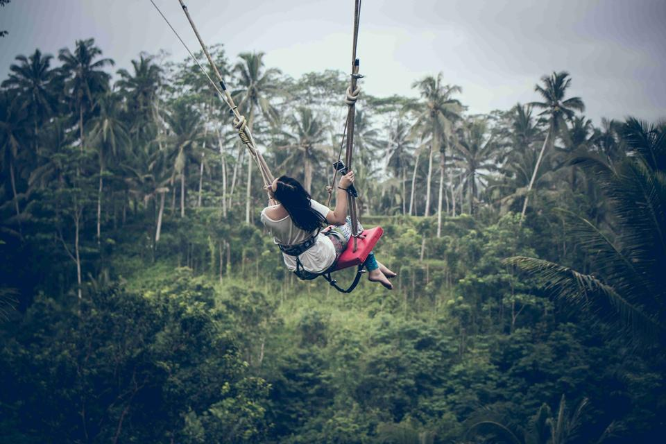 Woman swinging in the jungle of Bali island