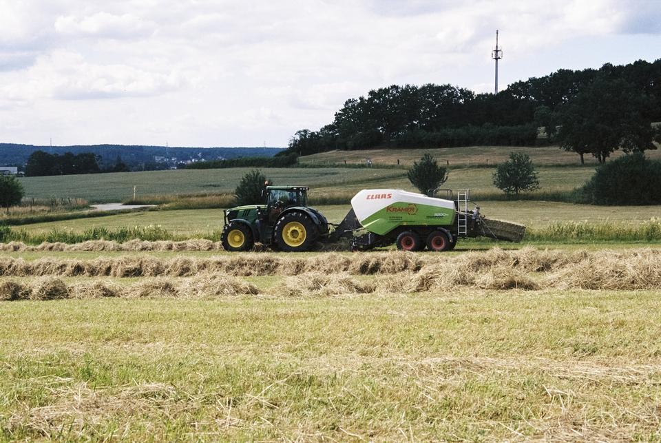 농부 화창한 날에 tractores에 의해 건초를 수확.