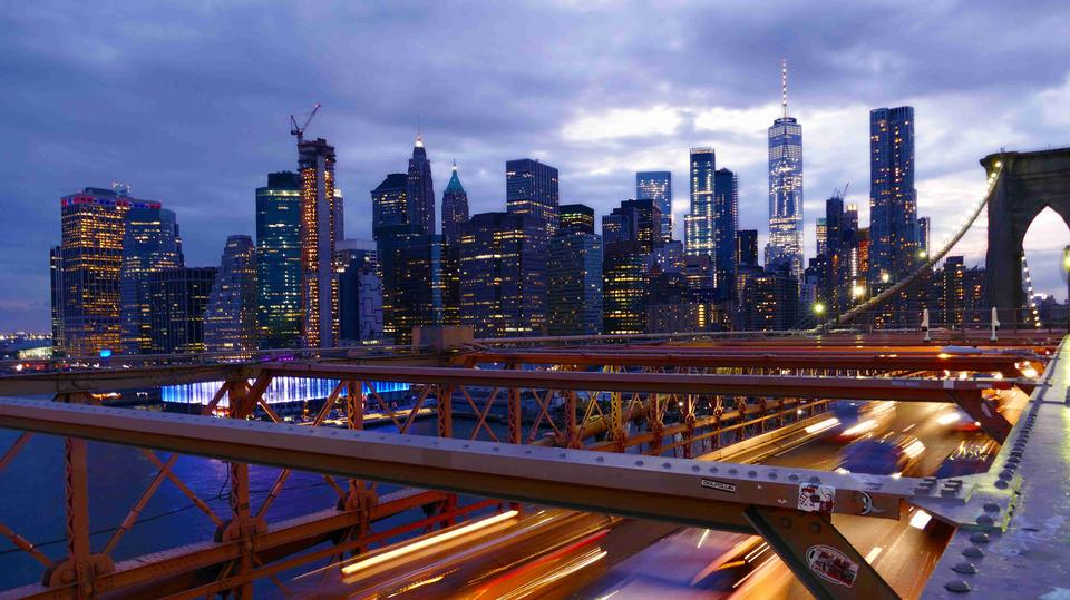 Автомобили несутся на закате на Бруклинском мосту, Манхэттен.