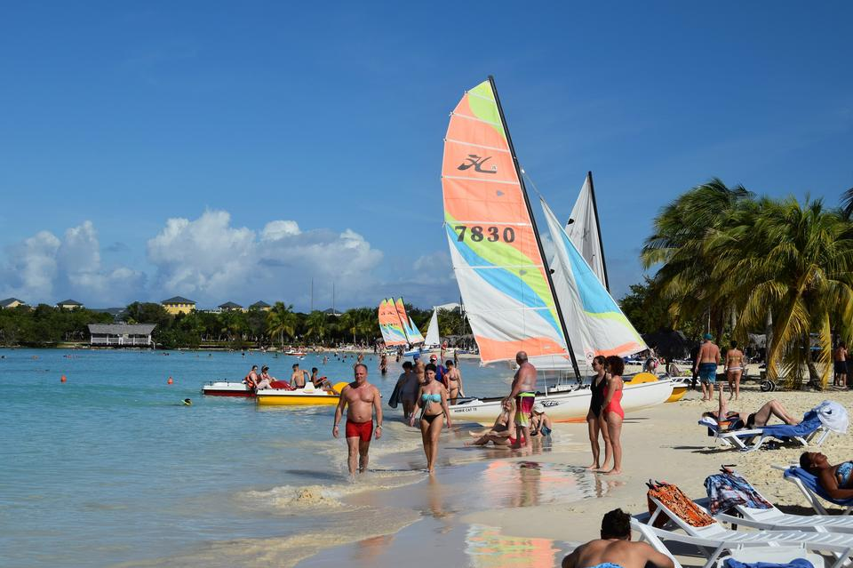 Colorful kayaks and sailing boats on a tropical beach in Cuba