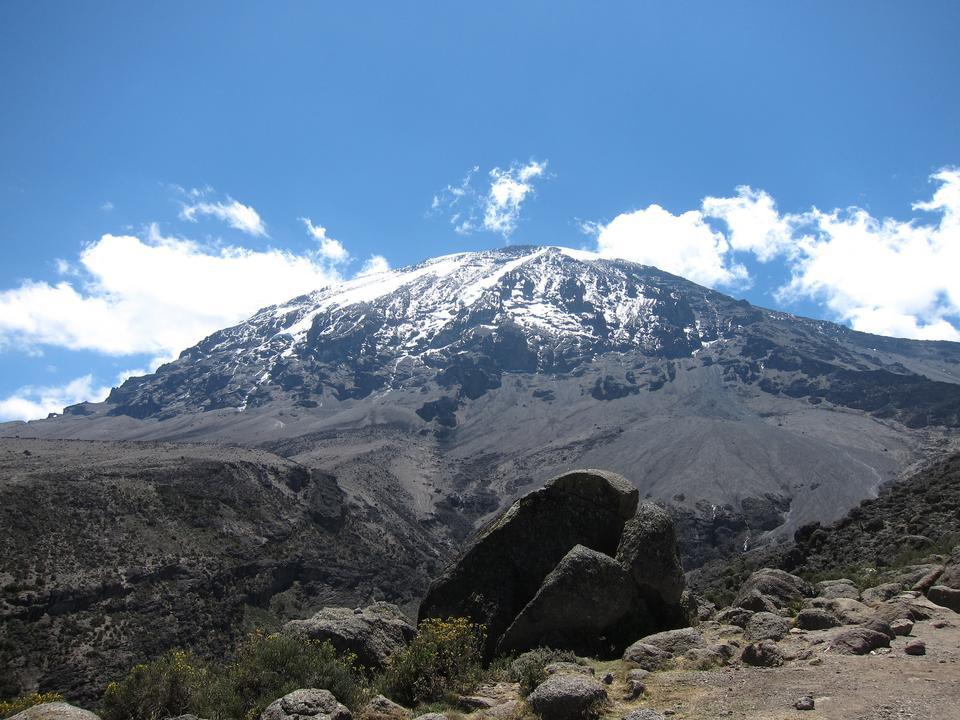Kilimanjaro mountain Tanzania snow capped under cloudy blue skies