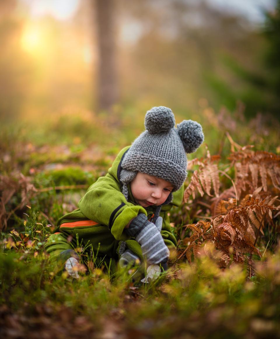 A little girl sitting on green grass