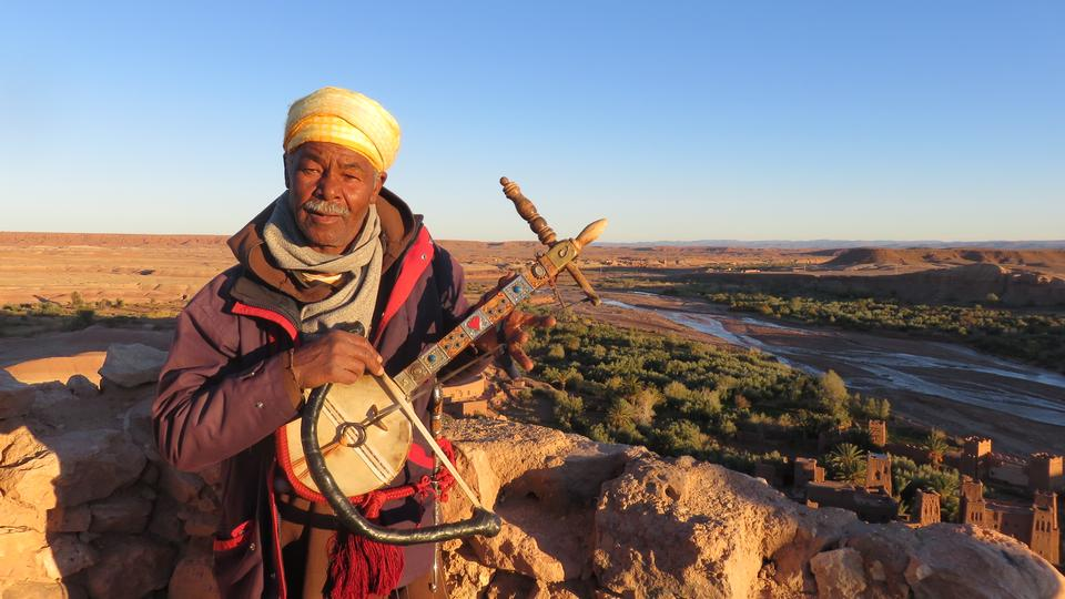 Local Bedouin carrying traditional musical instrument