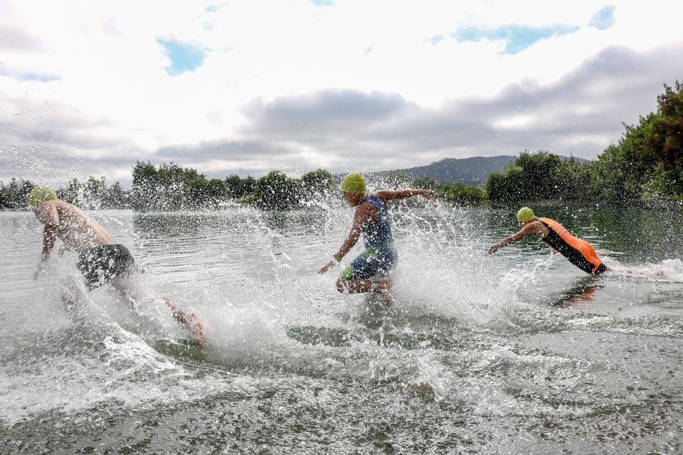 Drei Triathlon-Teilnehmer laufen ins Wasser zum Schwimmen