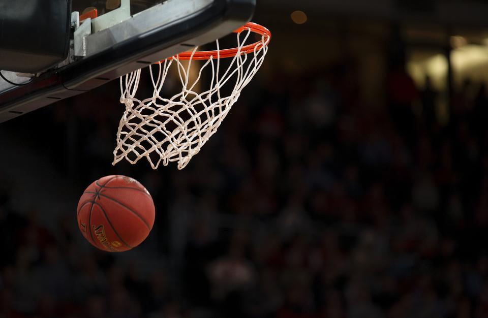 Der orange Basketballball fliegt durch den Korb