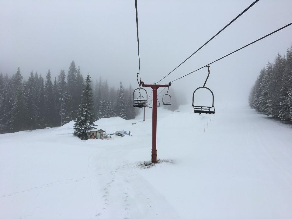Ski lift with seats going over the mountain and paths