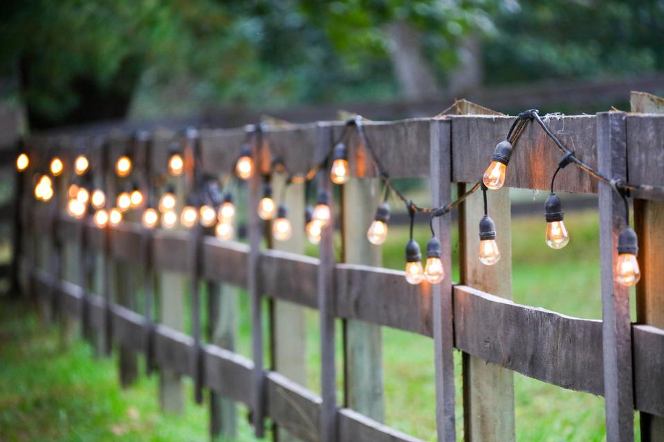 String of lights, exterior, yellow bulbs on old wooden Fence