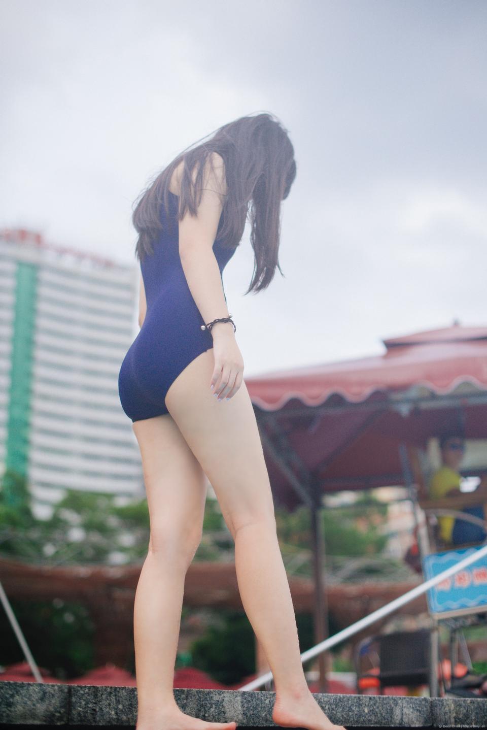 Красивая девушка в купальных костюмах отдыхает у бассейна
