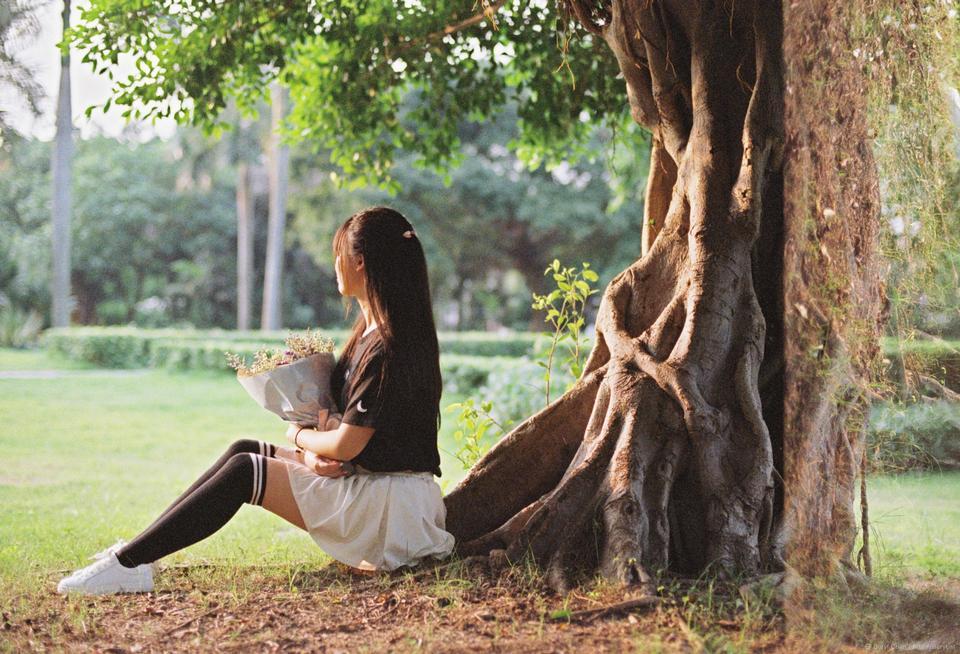 在樹下的美麗的女孩在庭院裡