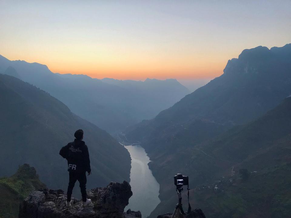 Fotógrafo profesional toma fotos con cámara en trípode.