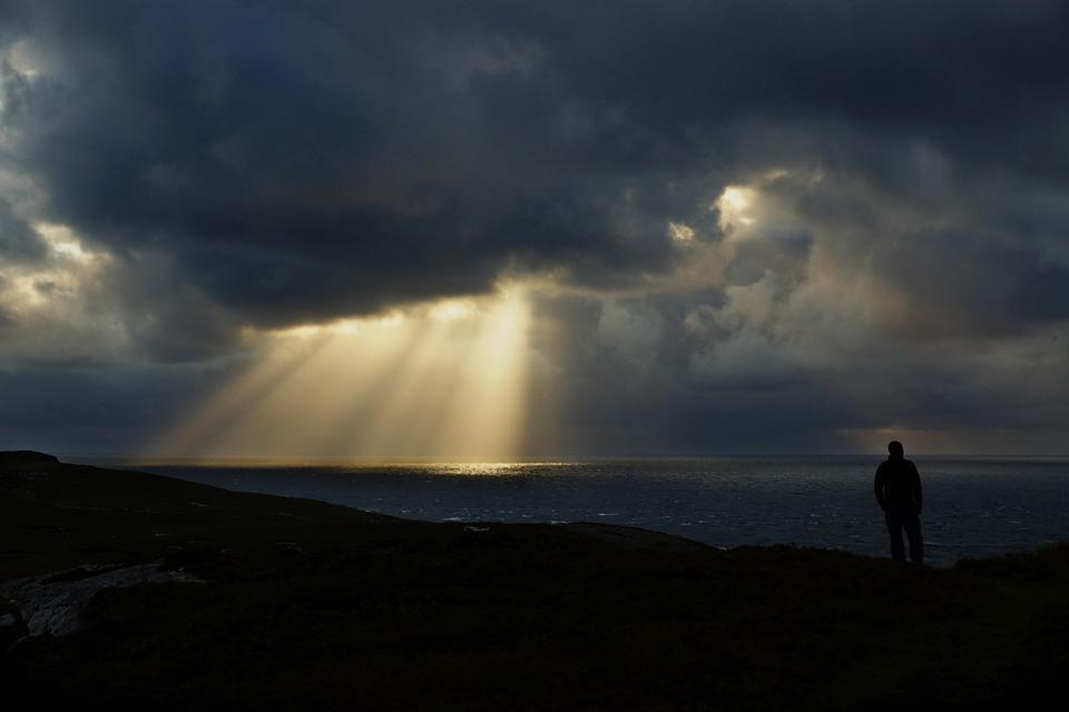 Un hombre en una silueta contra los rayos del sol.