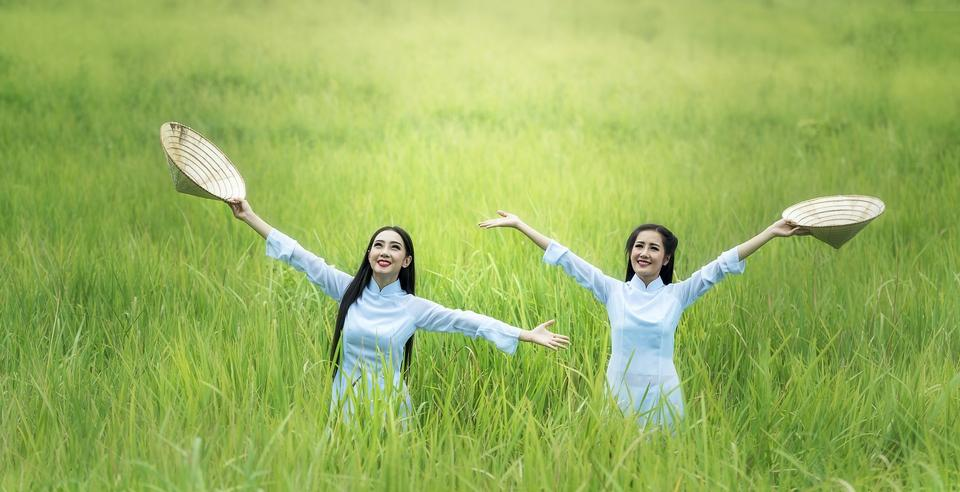 Two young women smiling and raising hands up on sunris background