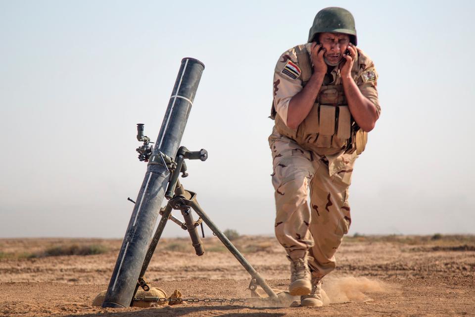 Сотрудник иракских сил безопасности стоит в стороне