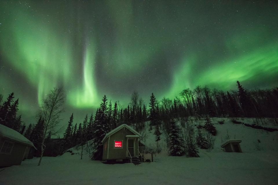 Aurora dances and shimmers overhead above a cabin at Coal Creek
