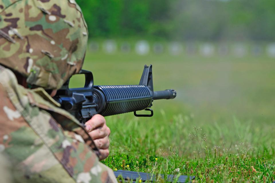 soldier aiming machine gun at firing range.