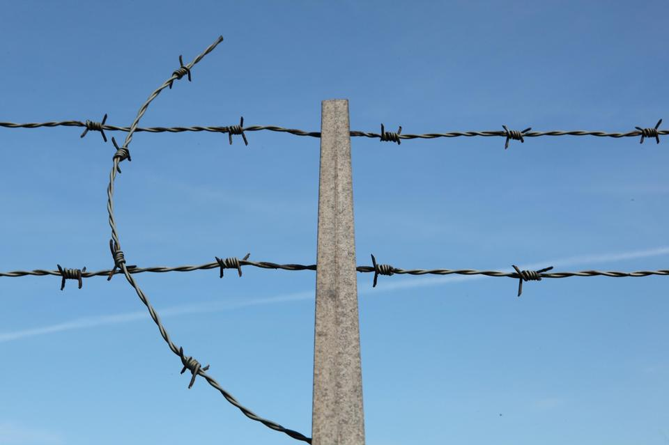 Barbed wire on fence with blue sky