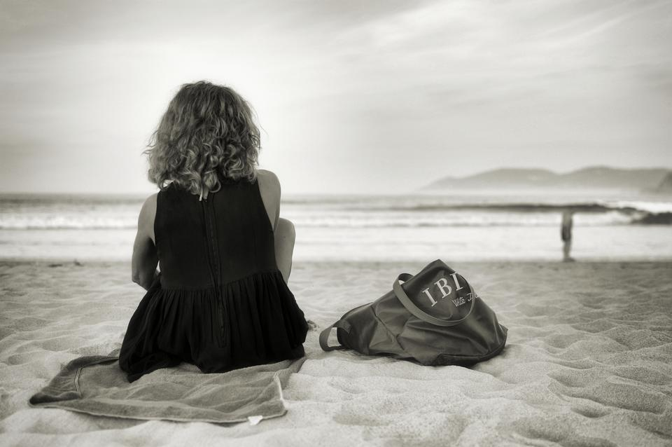 A young slim woman seated on a black sand beach