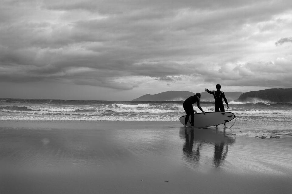 Happy surfers couple running with surf boards on the beach