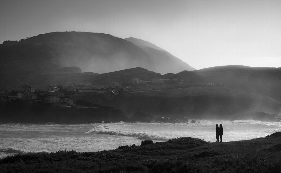Montage noir et blanc d'un homme pêchant sur la plage