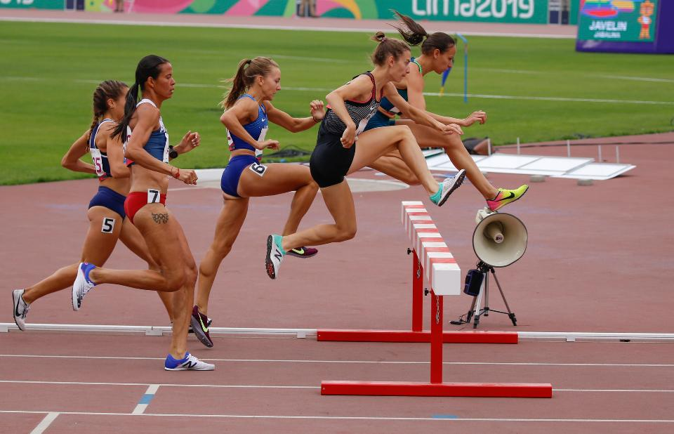 Female sprinter leaping over hurdles