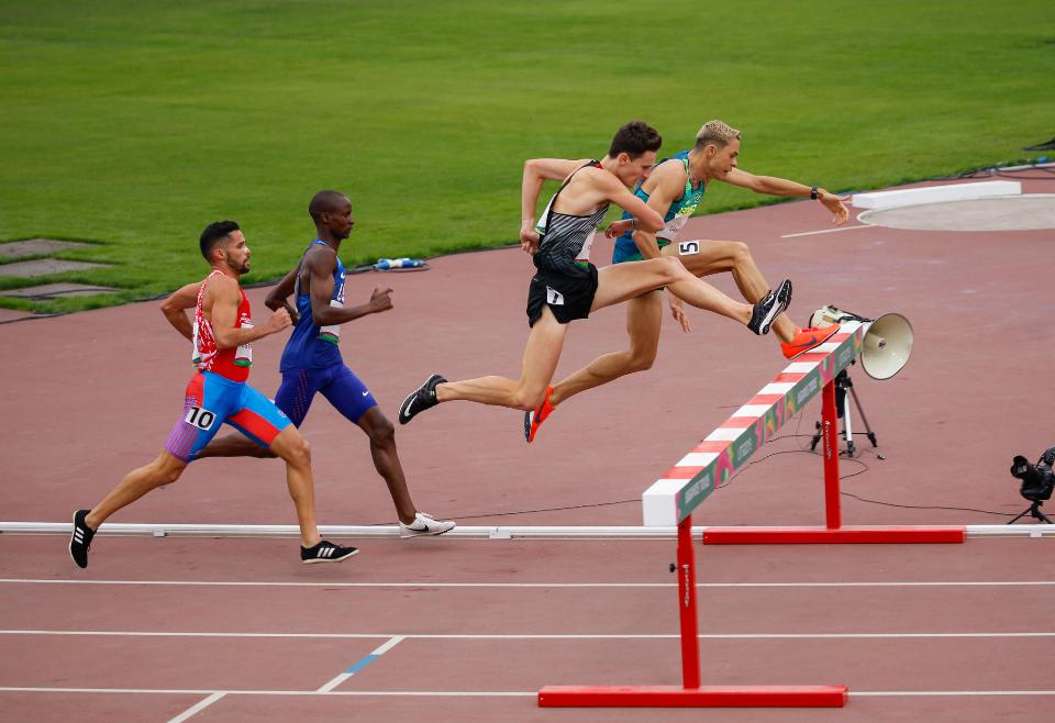 Male sprinter leaping over hurdles