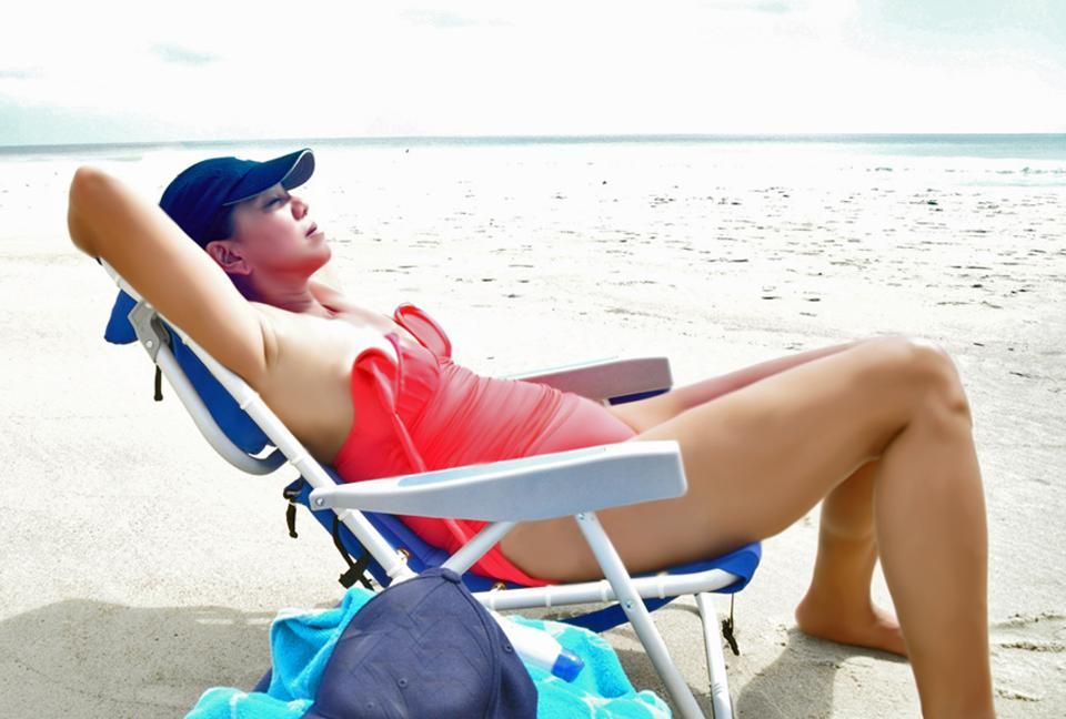 Happy young woman relaxing on deck chair at beach