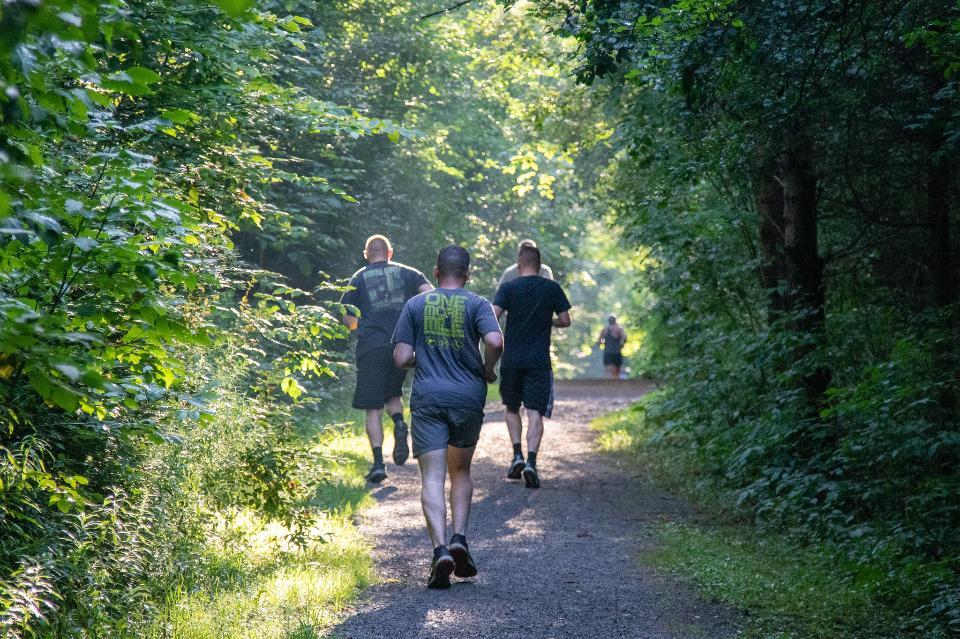 Gruppe junge Leute schleppen das Laufen auf einem Gebirgspfad