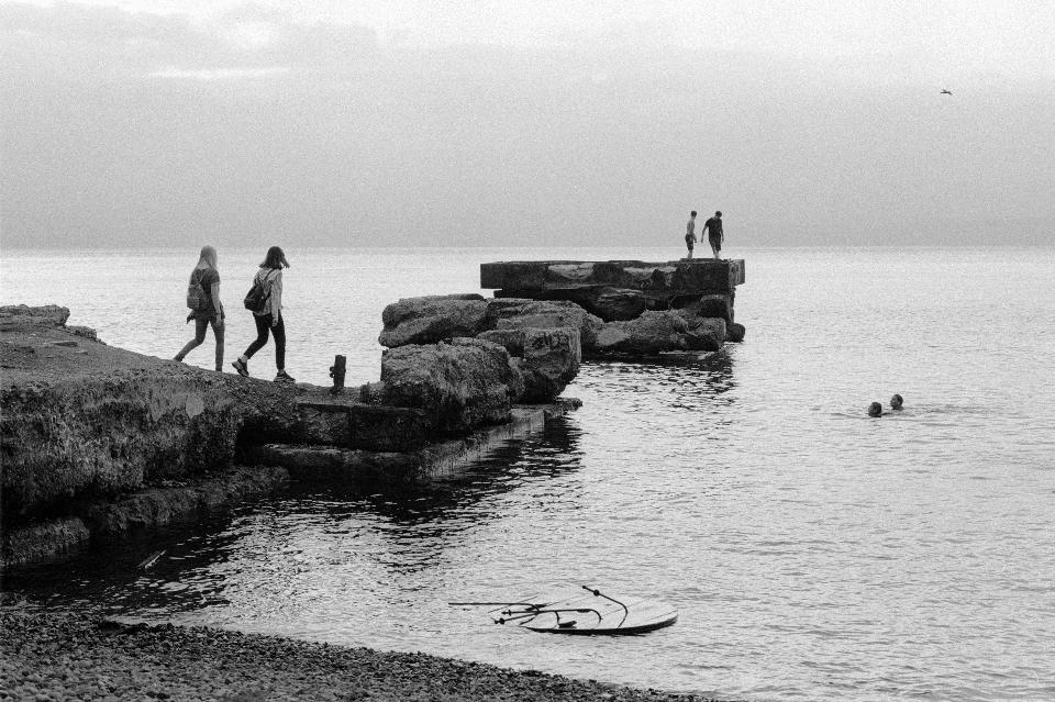 Black and white view of women walking together on rocky beach