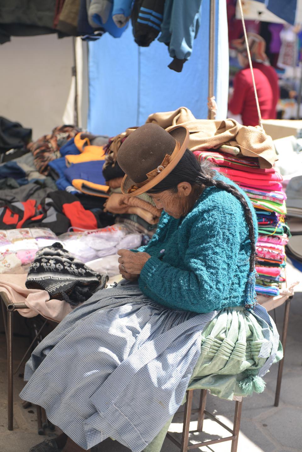 伝統的な衣装を編むボリビアの女性