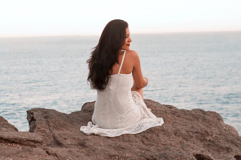 海の岩の上に座っているセクシーな女性