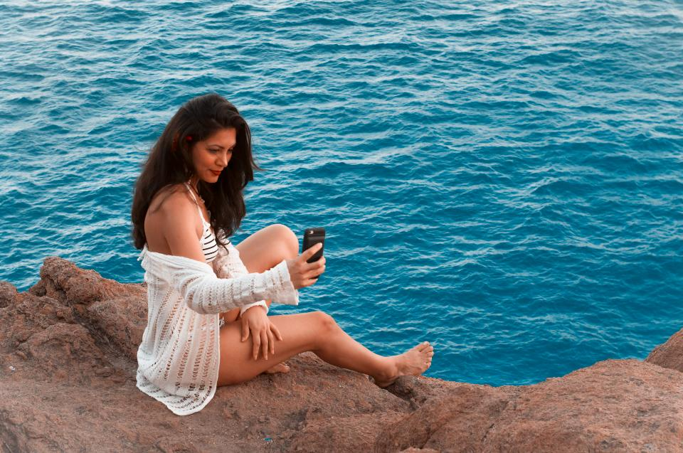 Sexy female sitting on the rock in the sea