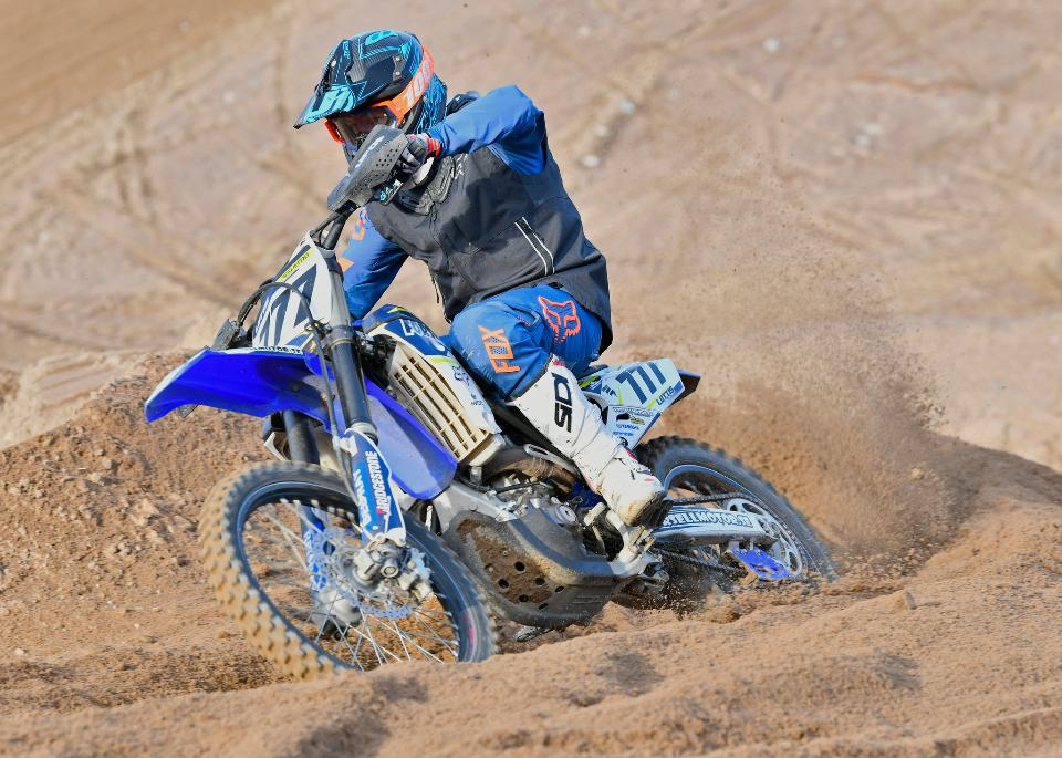 Motocross rider accelerating in curve in dirt track